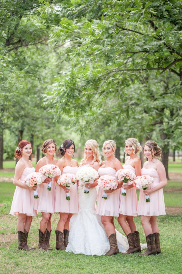 bridesmaids in knee length pink dresses and boots