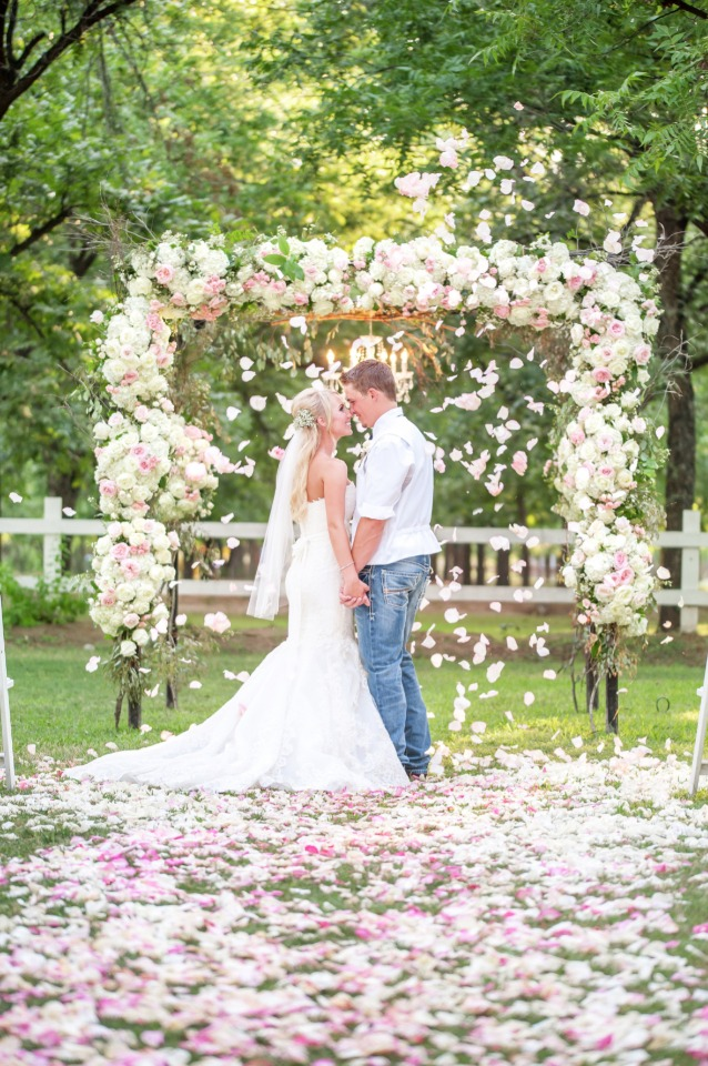 raining flower petals under this glam floral wedding arch