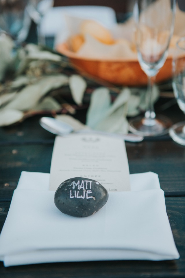 simple and elegant place setting with river stone escort card