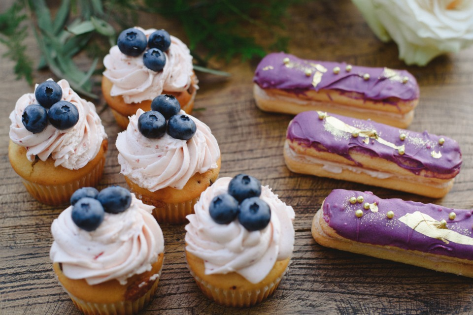 blueberry topped cupcakes and purple and gold eclairs