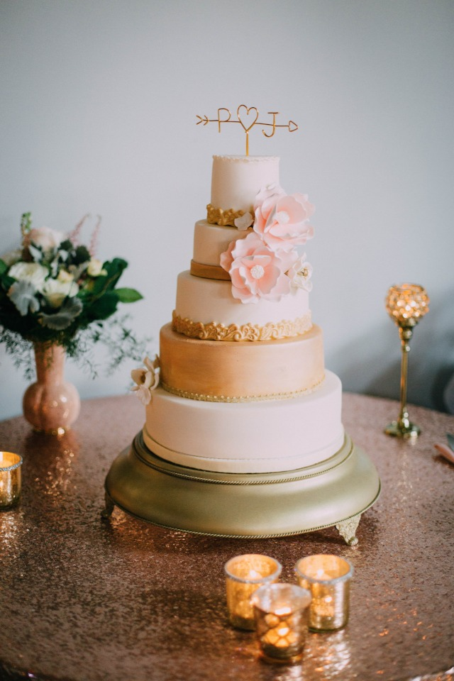 gold and white wedding cake with pink sugar flowers