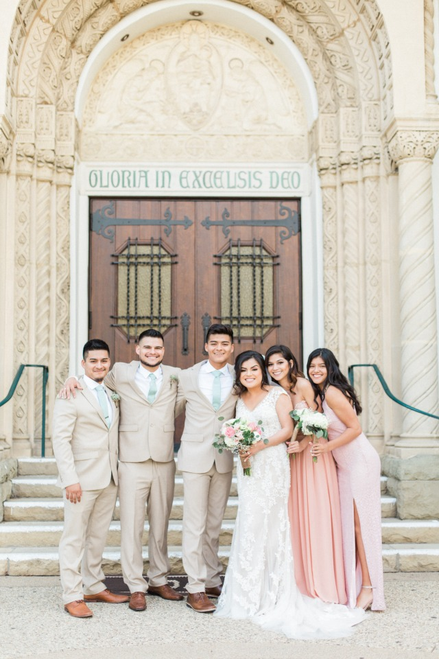 bridesmaids in long pink dresses and groomsmen in neutral and sage