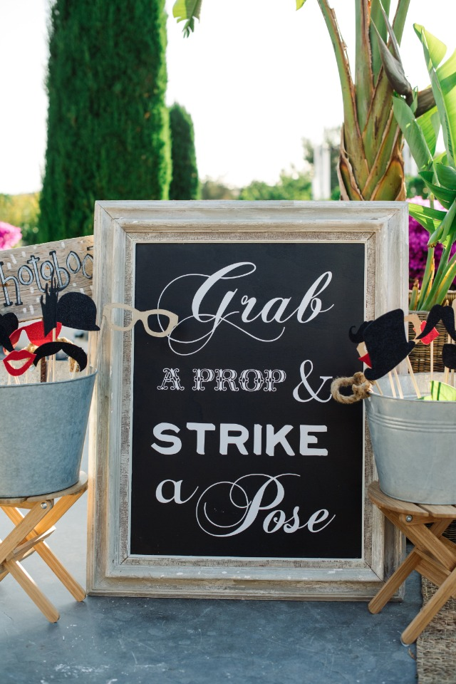 grab a prop and strike a pose photo booth sign