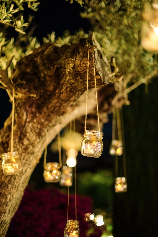 candle lit mason jars hanging from garden trees