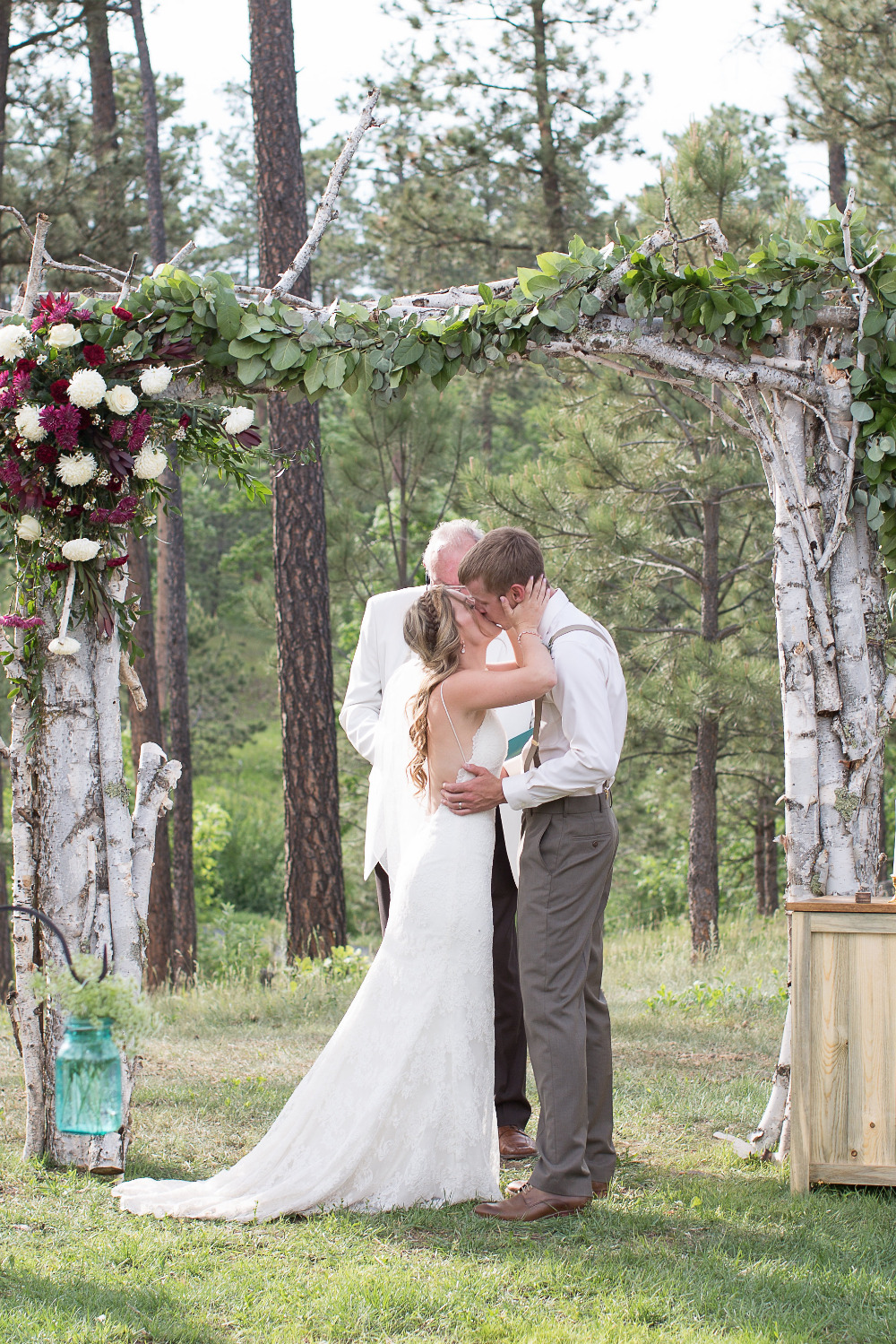 wedding kiss with wooden wedding arch