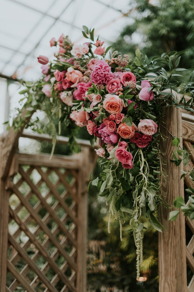 pink and peach flower accented wedding arch
