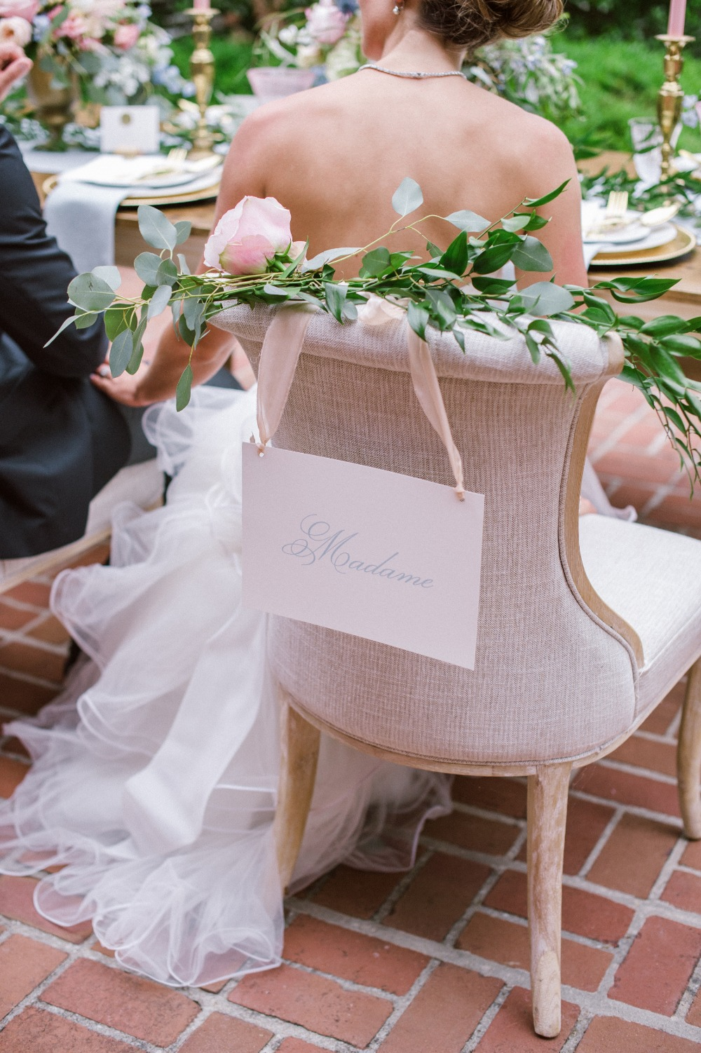 Madame brides wedding seat sign with flower garland draped chair