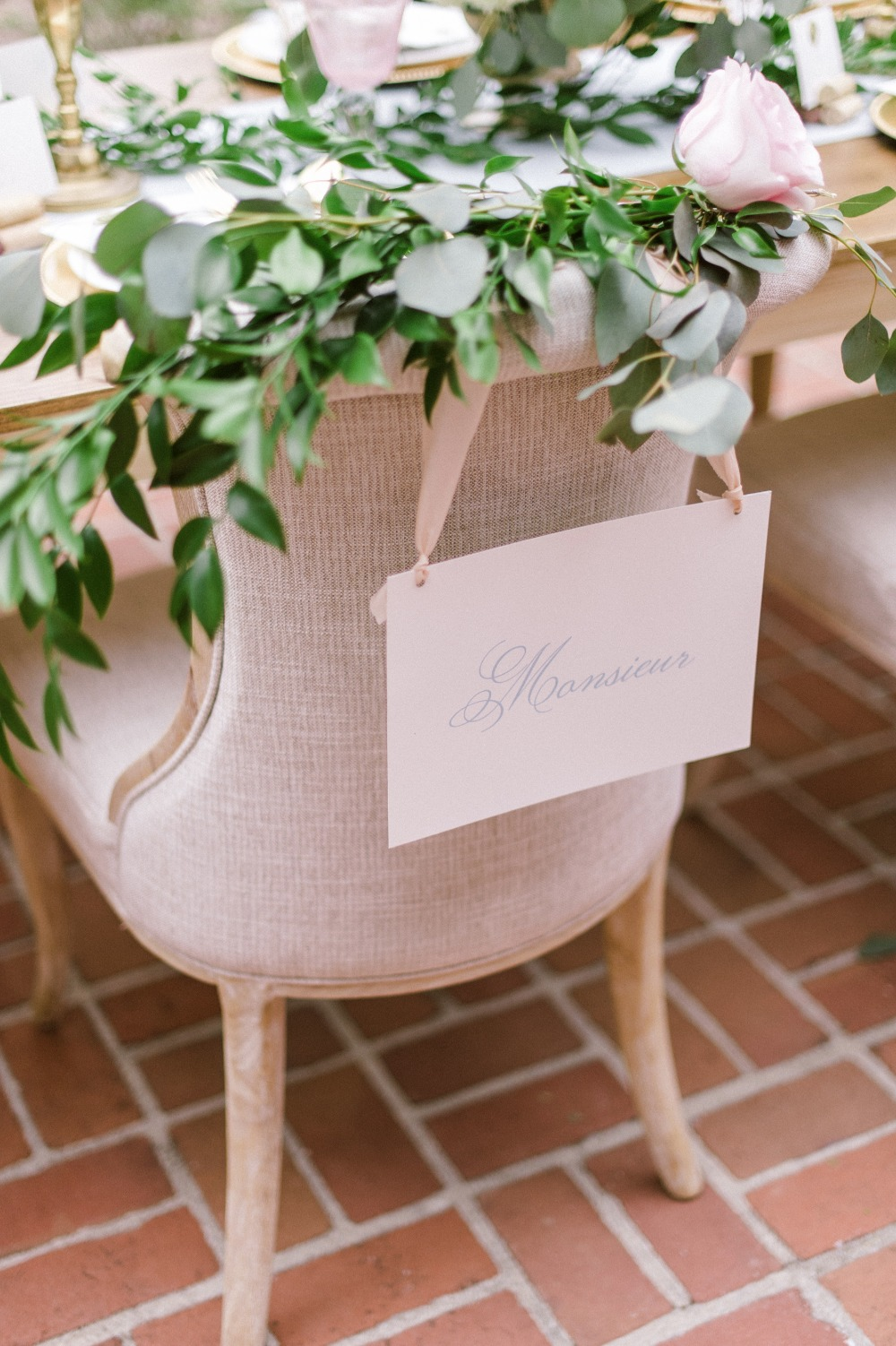 Mounsieur groom seat sign draped in a flower garland