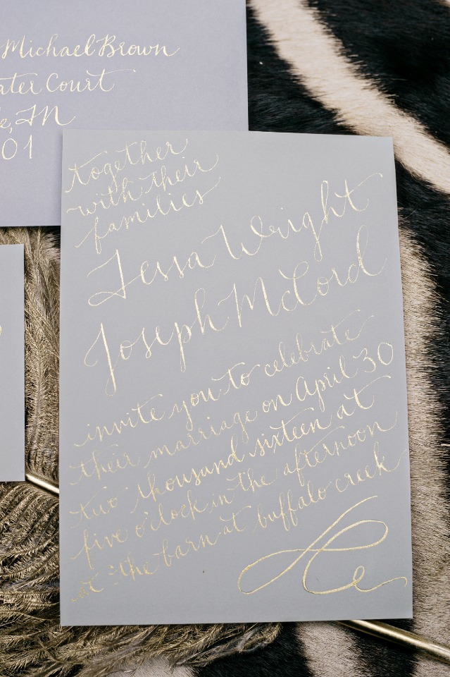 gold calligraphy wedding invite on grey paper