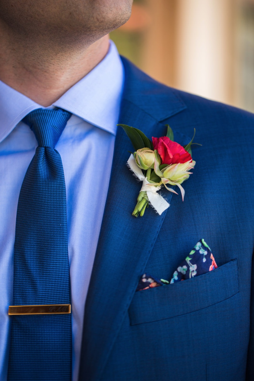 Blue suite with a pink flower boutonniere