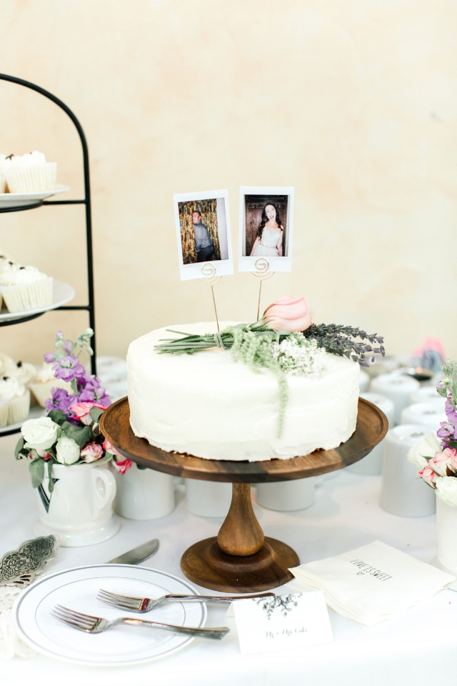 single tier wedding cake with simple and elegant flower accent and fun polaroid topper