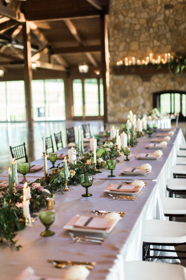 family style seating with garland and candles decorating the table