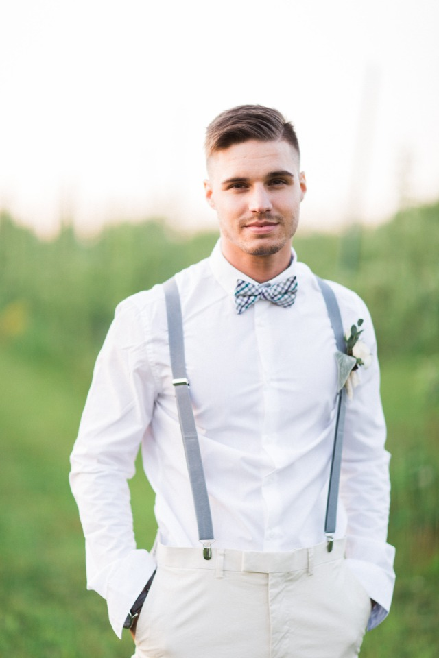 groom in dusty blue suspenders and bow tie