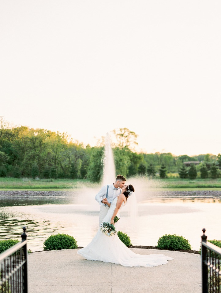 romantic wedding kiss in front of a fountain