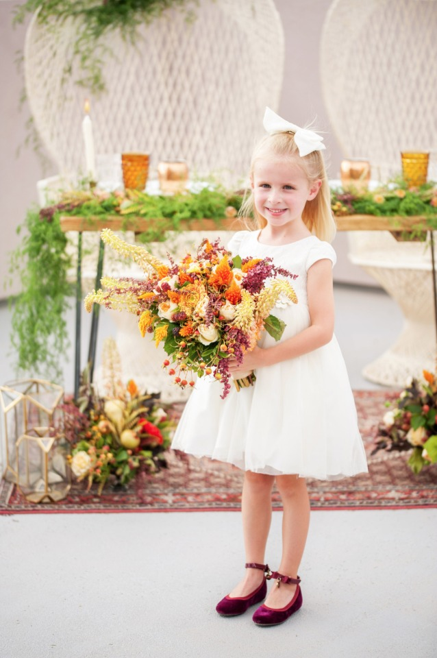 sweet little flower in burgundy flats with a fall bouquet