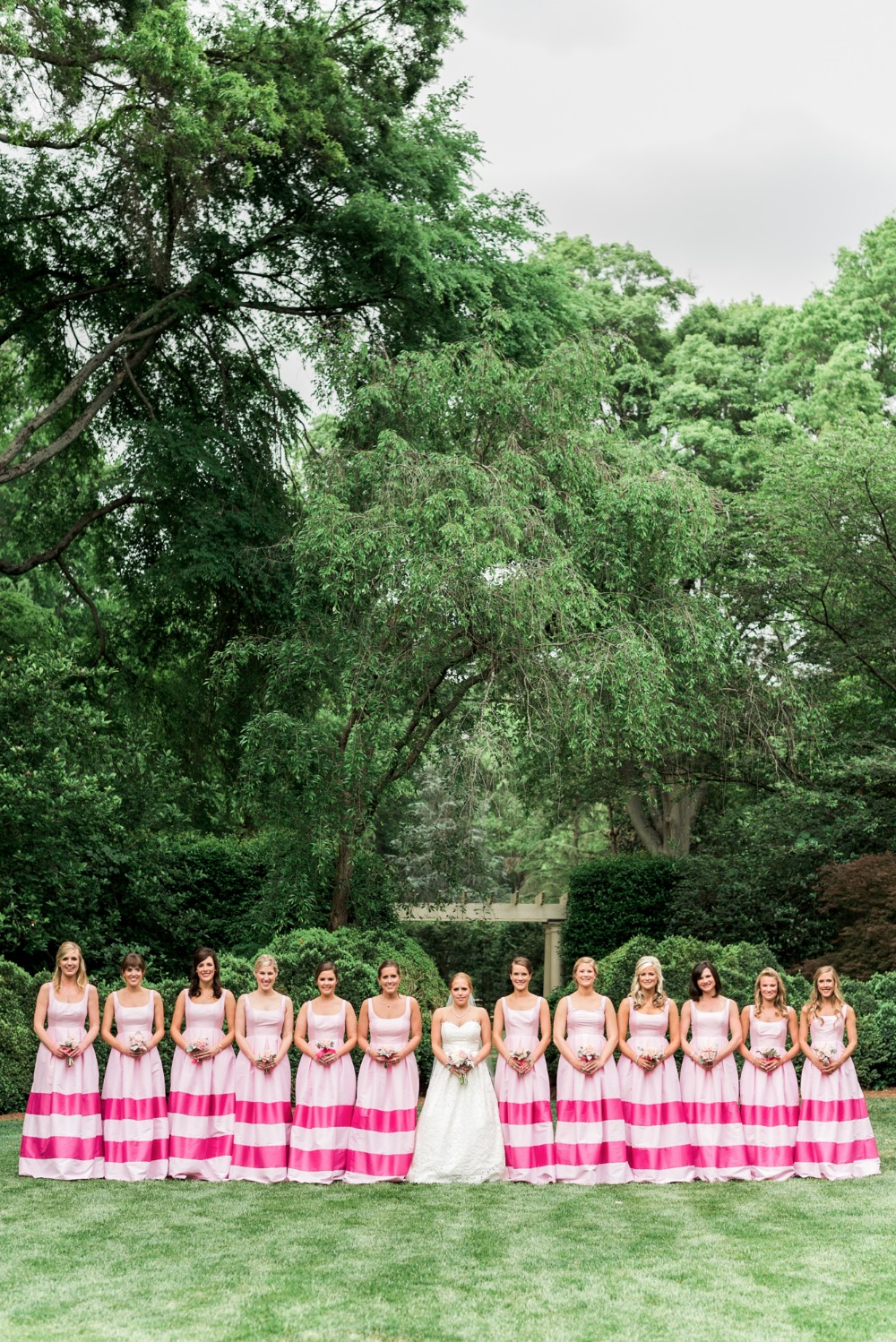 Bridesmaids in matching pink striped gowns