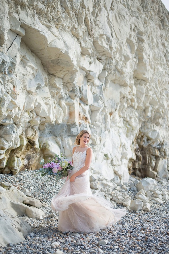 happy bride on a rocky beach