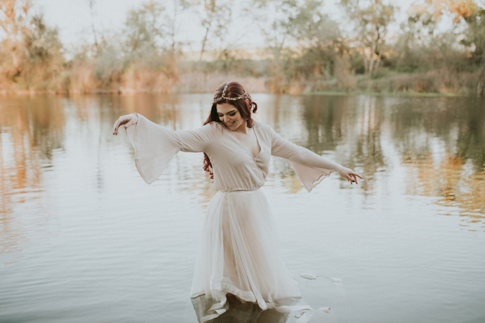 boho bride having fun in the creek