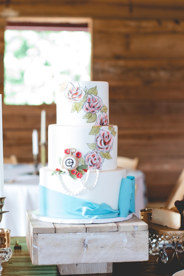 Floral painted wedding cake with blue bow