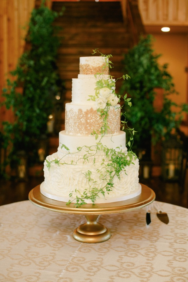 Gold and white wedding cake with green garland