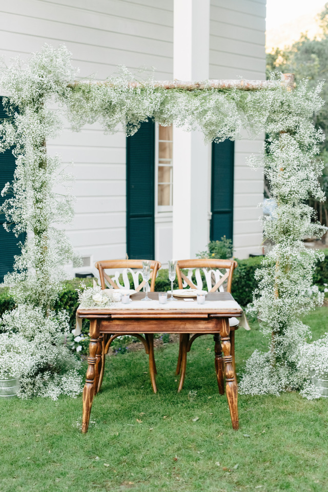 wood sweetheart table with babys breath backdrop