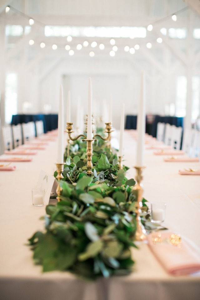 family style seating with long garland and gold candle stick centerpiece
