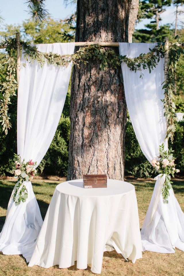draped wedding ceremony backdrop with floral garland
