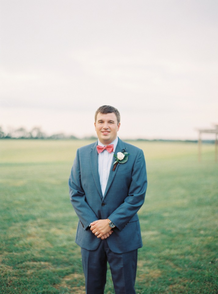 groom in blue with red bow tie
