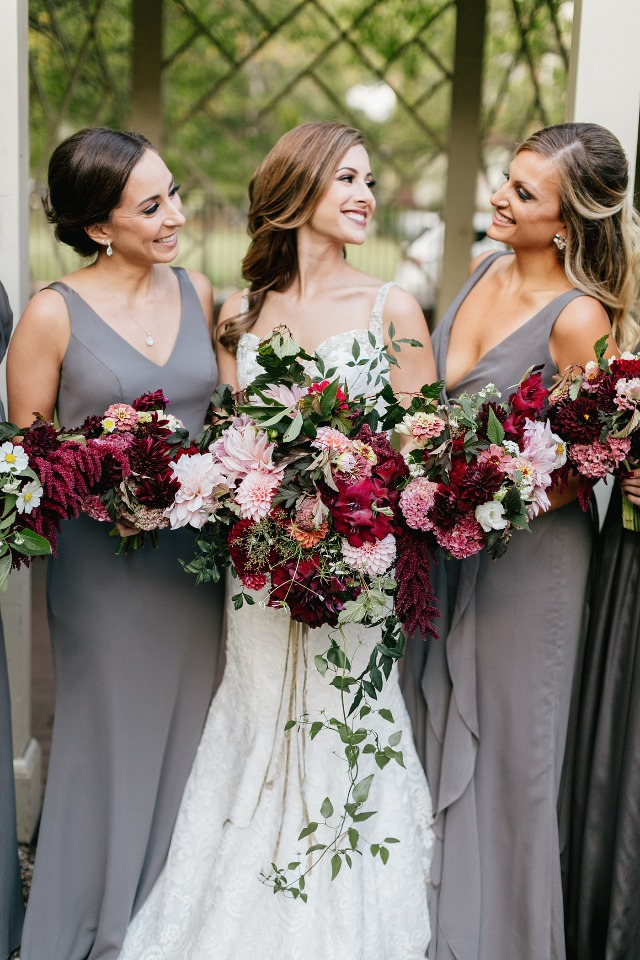 bridesmaids in full length grey dresses and burgundy bouquets