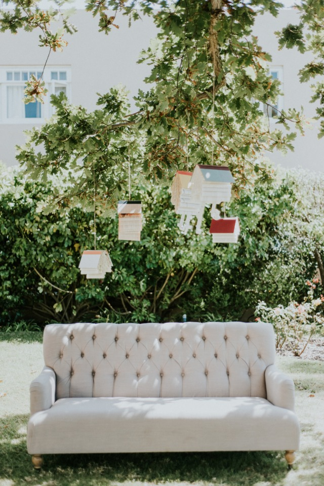 Photo booth with vintage couch and hanging books