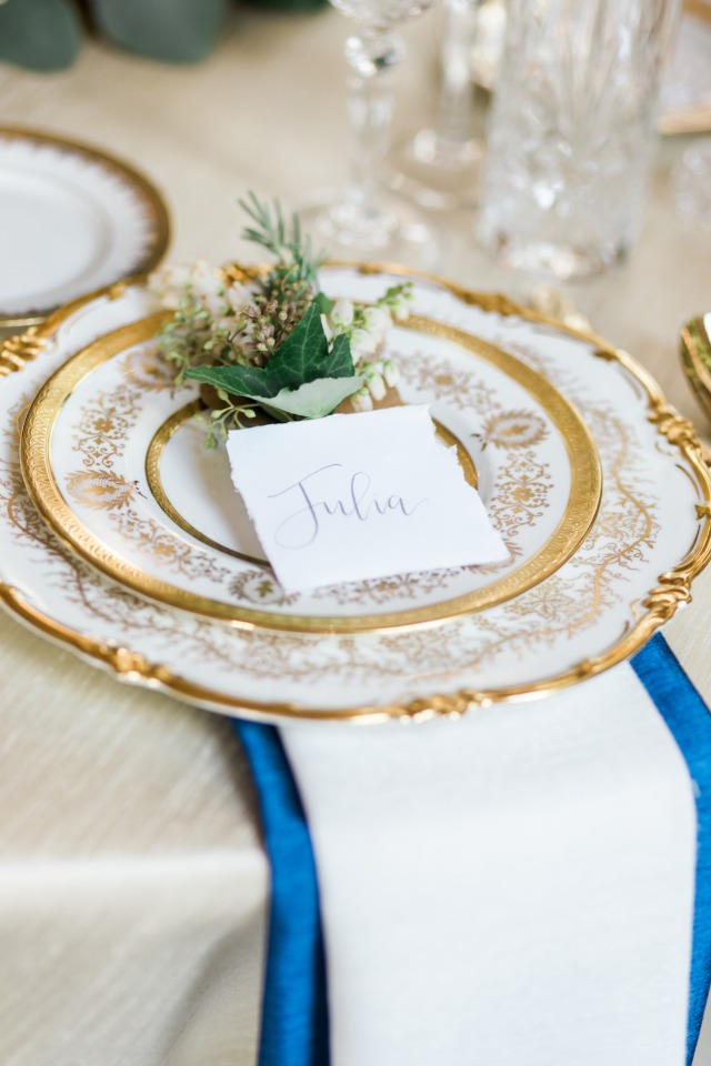royal looking gold and white place setting with royal blue linen accent