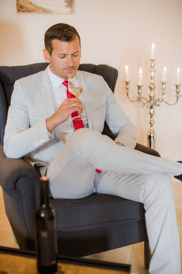 groom in sandstone suit with red tie