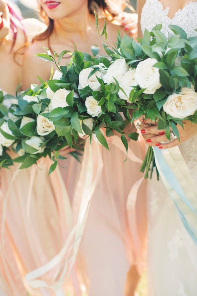 bridesmaids with matching white and green bouquets