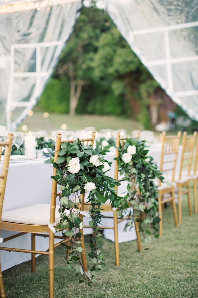 bride and groom wedding seats decorated in white flower garlands