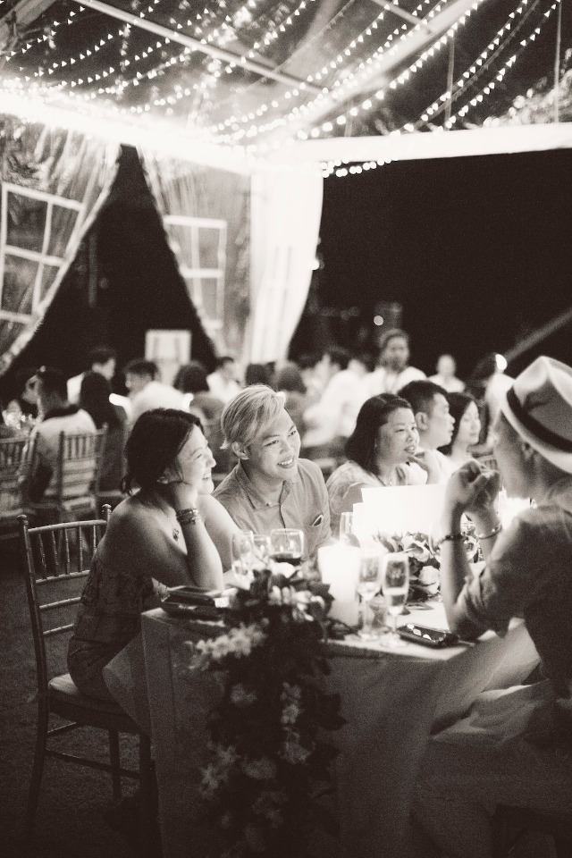 outdoor wedding reception lit up under a giant tent