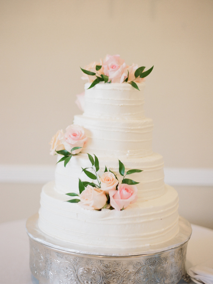 classic white wedding cake with pink roses