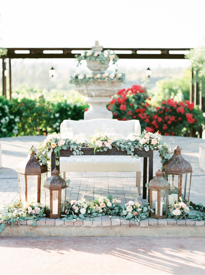sweetheart table draped in flowers with giant lanterns