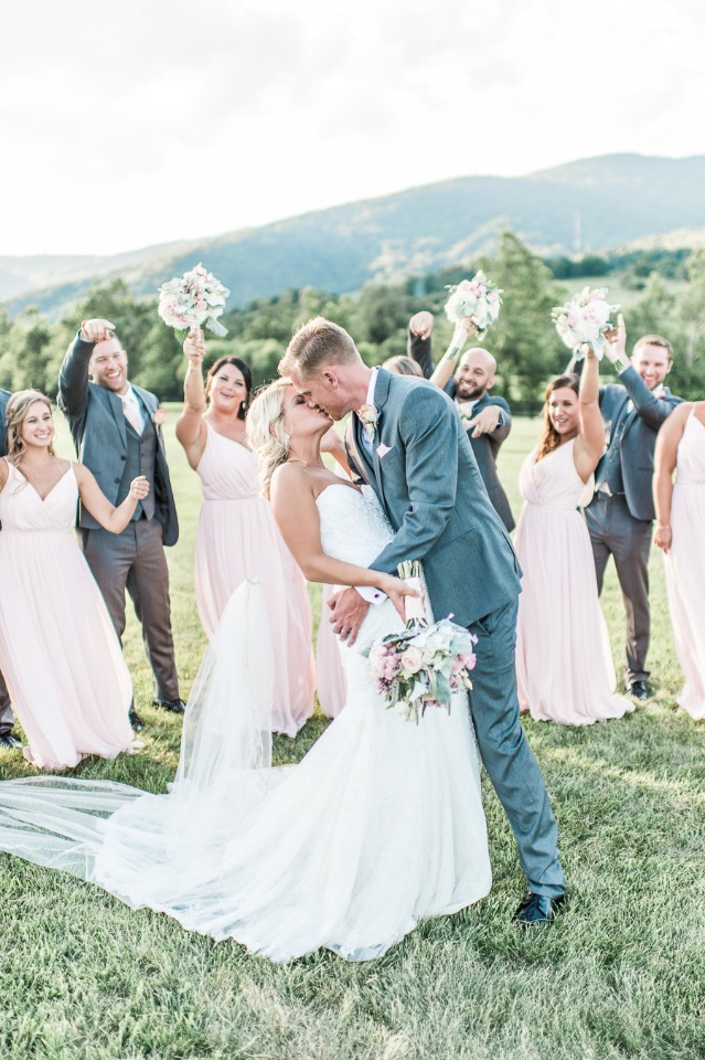 Wedding kiss with bridal party