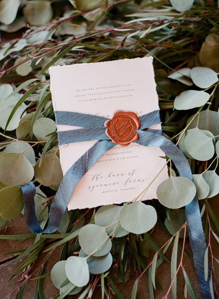 romantic wedding invite with wax seal wrapped in ribbon
