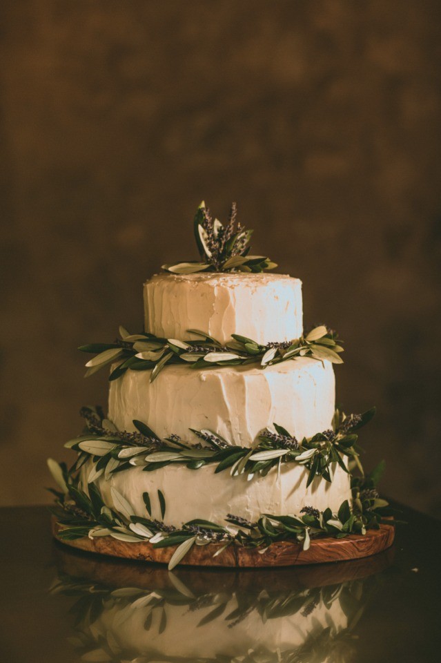 wedding cake topped with olive branches and lavender