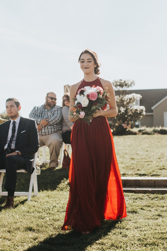 bridesmaid in red dress and white and pink bouquet