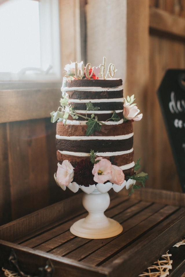 chocolate naked cake topped with a glittery gold we do topper