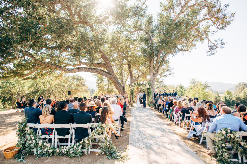 wedding ceremony with floral chair garlands