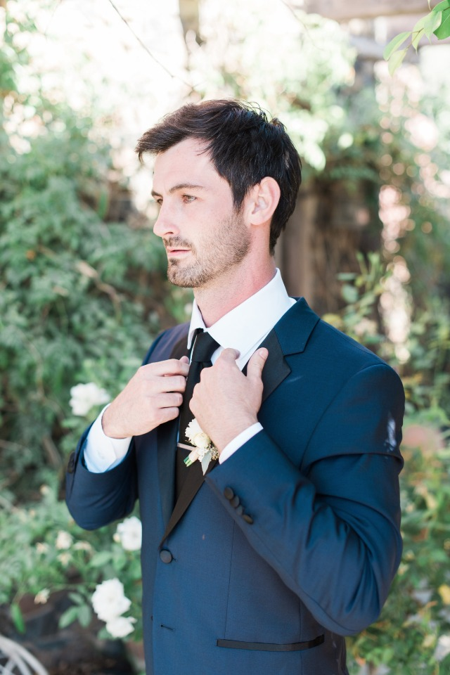 groom in navy and black tuxedo