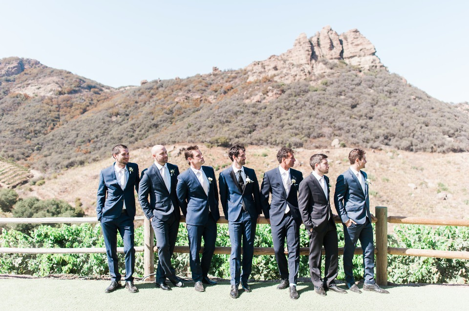 groomsmen in mismatched blue and grey suits
