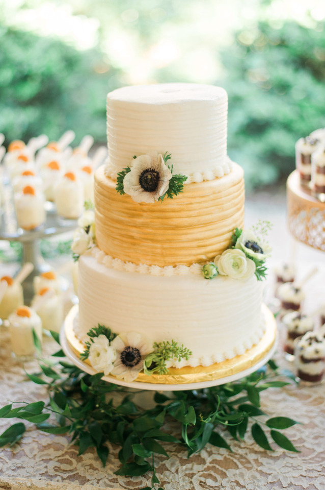 gold and white wedding cake with anemones