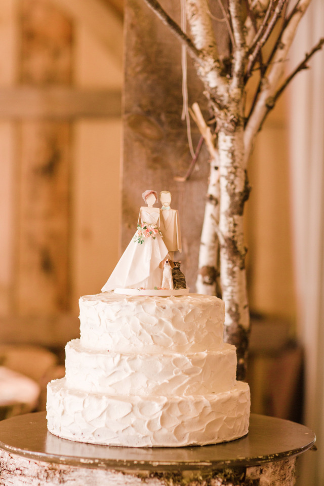 white rustic wedding cake with cute topper