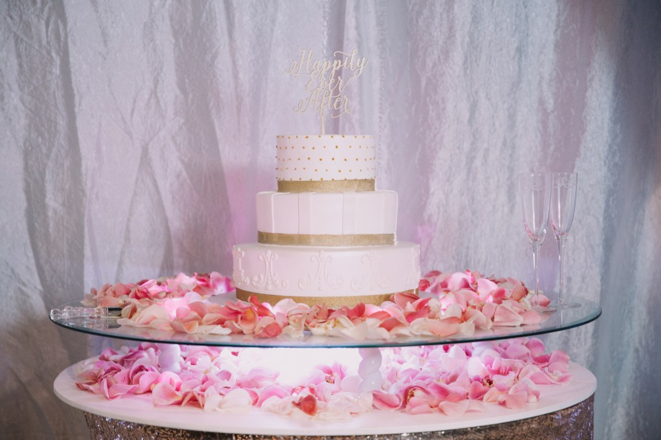 White and gold cake with pink rose petals