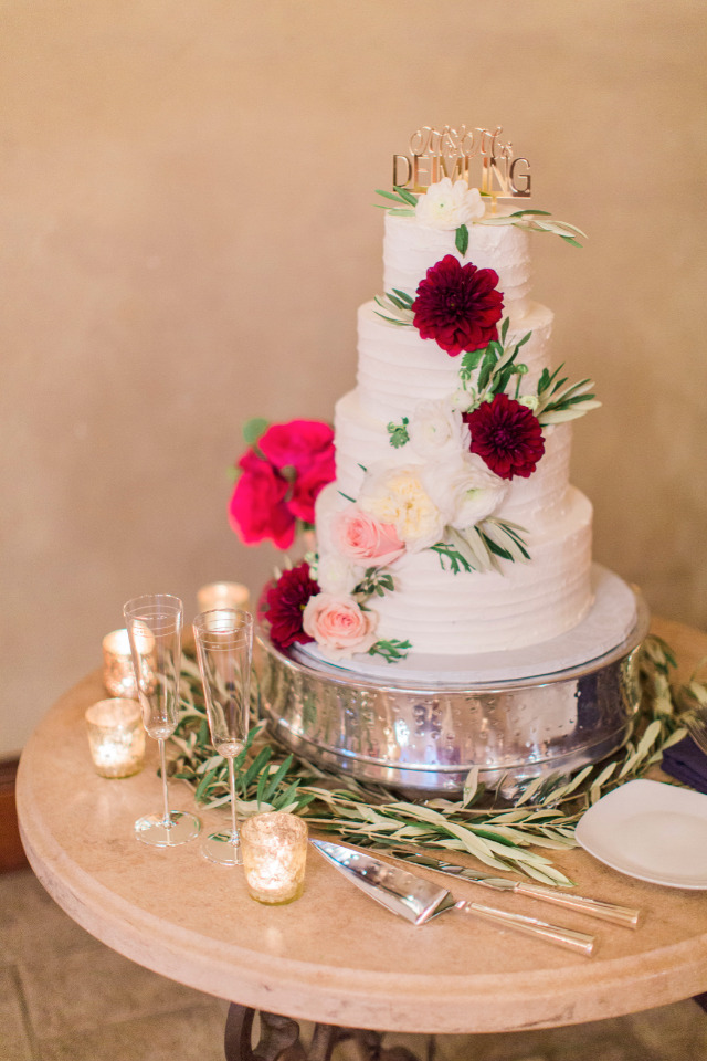 white wedding cake with flowers and gold topper