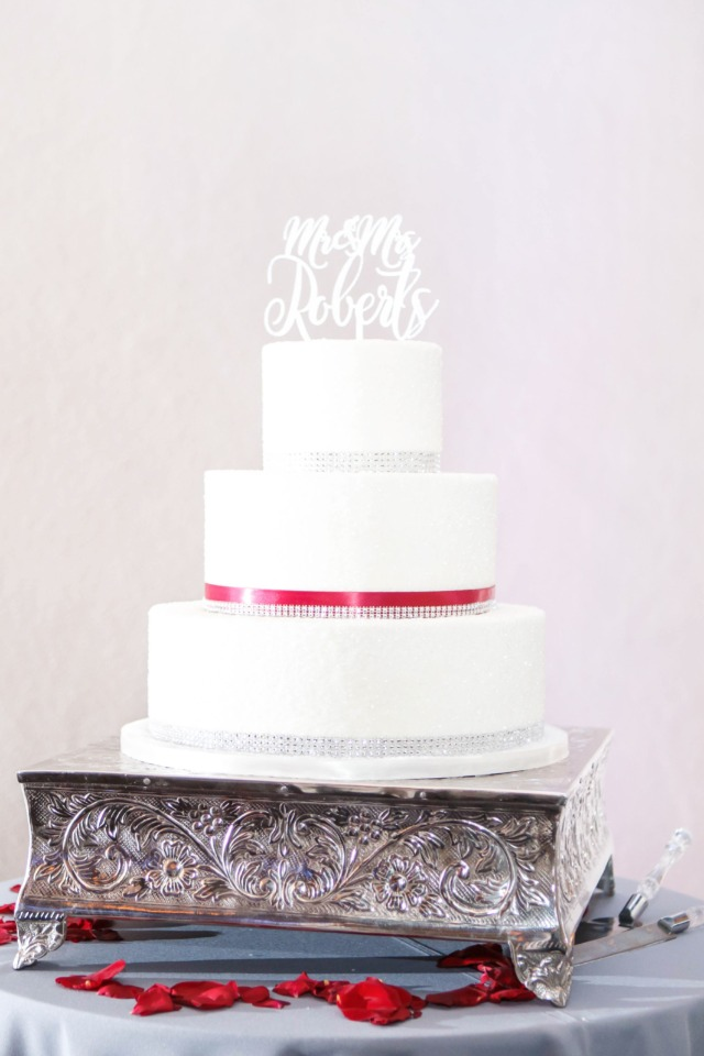 Elegant white cake with red ribbon and crystals
